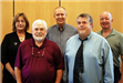 Image of five commissioners standing and smiling for camera