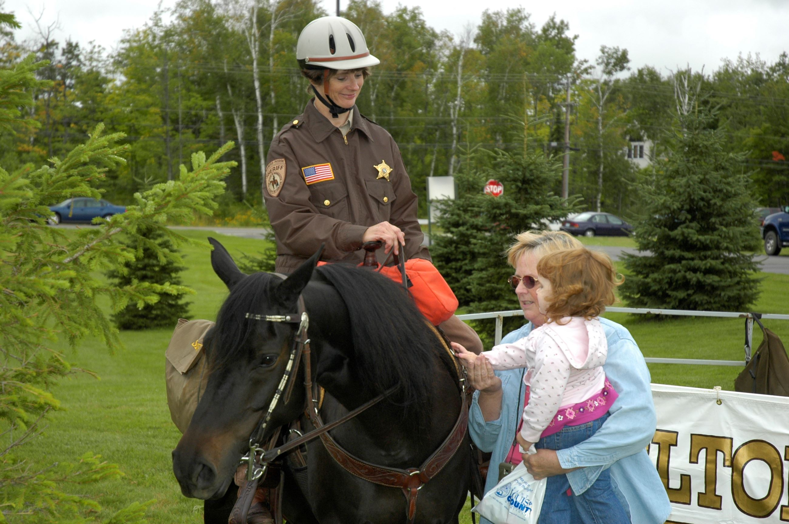 Female officer on a brown horse with a child petting horse