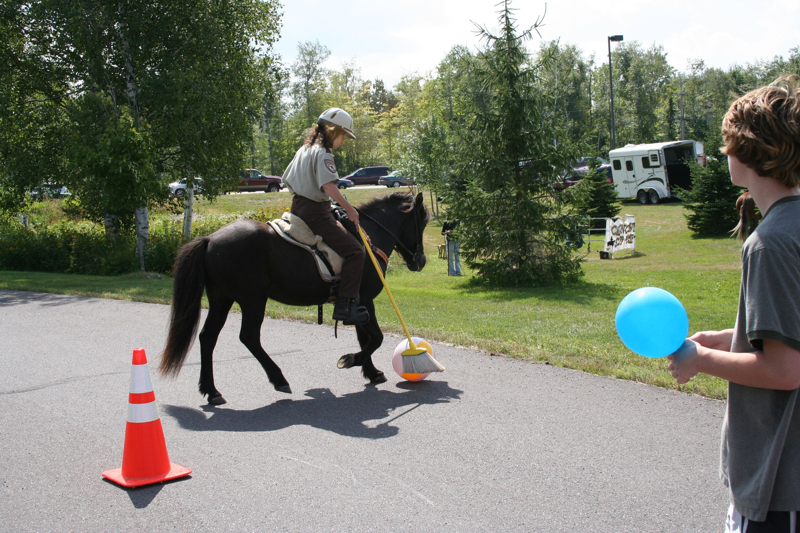 Mounted officer with broom and beach ball for obstacle course