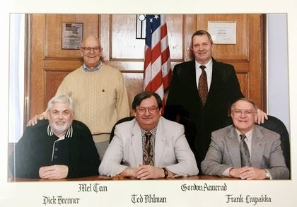 Five male commissioners sitting for camera